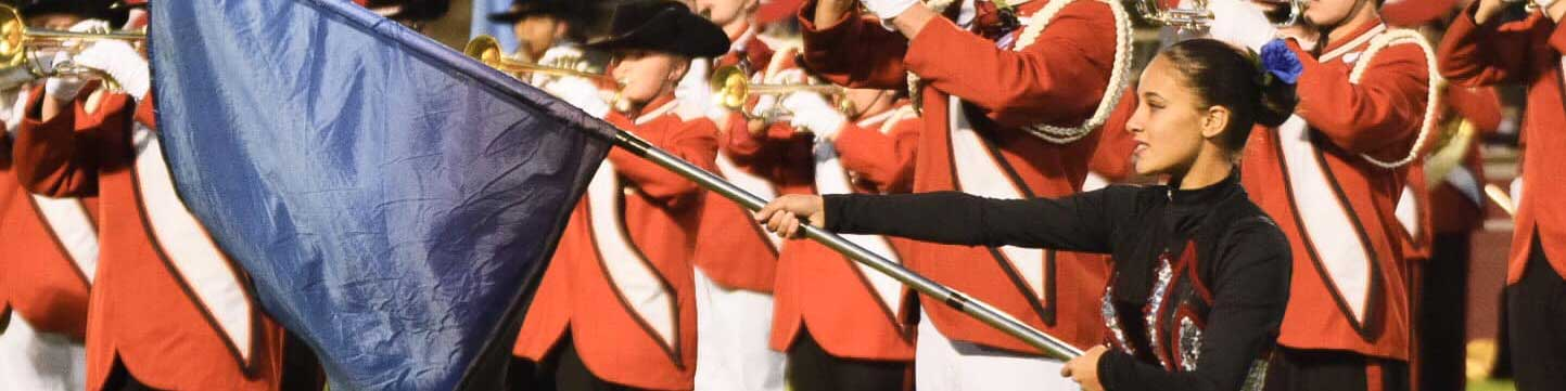 Marching band and a color guard member holding a flag